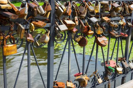 Love padlocks on the bridge. Wedding locks on a metal fencing. Love locks that couples hand on bridges to symbolize their true love. Kaliningrad - July 2017 Russian.