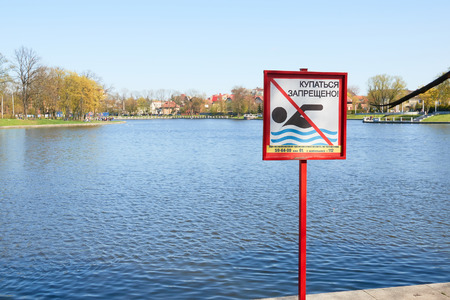 A sign to swim is forbidden on the shore of a lake in a city park in Russia. Text in Russian language.