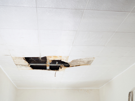 Ceiling panels damaged  huge hole in roof from rainwater leakage.Water damaged ceiling . Stockfoto