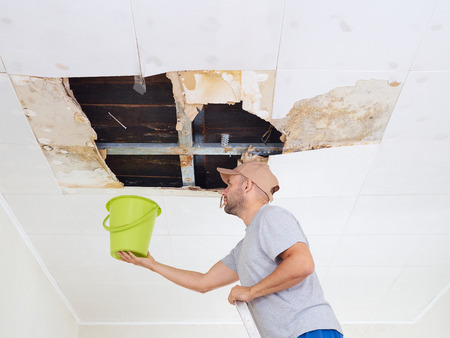 Man Collecting Water In Bucket From Ceiling. Ceiling panels damaged huge hole in roof from rainwater leakage.Water damaged ceiling . Banque d'images