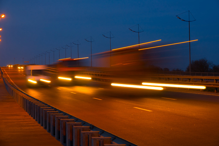 Highway traffic cars at night blured. Cars moving on road on bridge evening blurry. Banque d'images