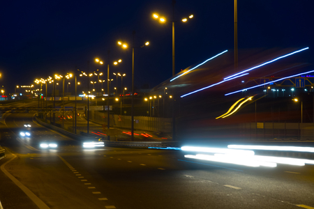 Highway traffic cars at night blured. Cars moving on road on bridge evening blurry. Stock Photo