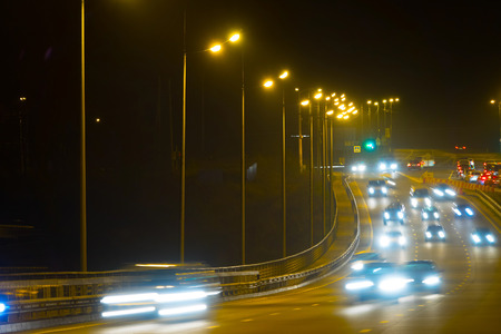 Highway traffic cars at night blured. Cars moving on road on bridge evening blurry. Stockfoto