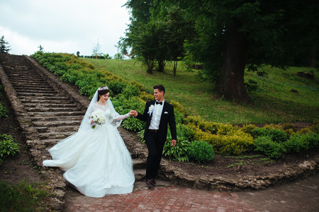 Amazing portrait of a wedding couple walking down the stairs and holding their hands.