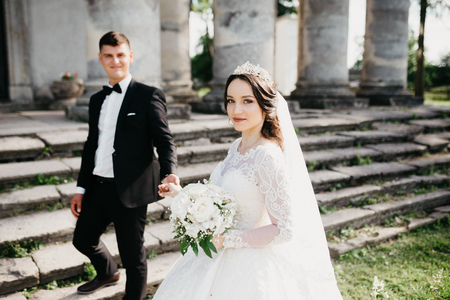 Great portrait of a wedding couple which walking to the old renaissance palace. They are looking at the camera and smiling.