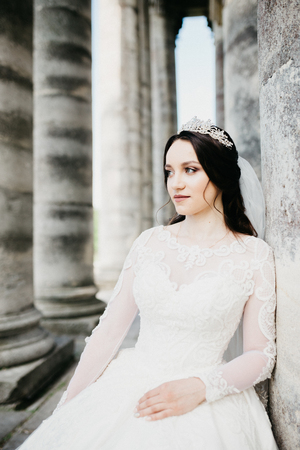 Wonderful portrait of a beautiful bride with a diadem on her head, she is standing nearby the old renaissance palace.