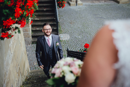 Portrait of a beautiful wedding couple. They are standing on a stairs  of an old building, a groom smiling and looking at his bride. We can see only a shoulder of a bride and her bouquet.