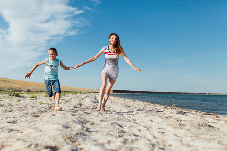 Funny portrait of a happy family on the beach. Mother is holding his son by the hand, they are running on the seashore, looking at the camera and smiling. Stockfoto