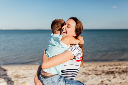 Funny portrait of a happy family on the beach. Mother is holding his son on her hands, they are embracing and smiling. Stockfoto