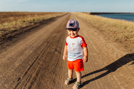 Portrait of a little boy on the road near the sea. He is standing on the road and smiling.