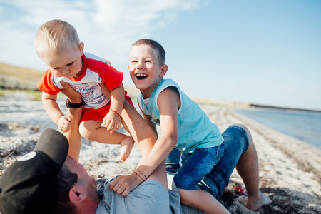 Funny portrait of a father and his sons, while they are playing on the beach, lying on the sand, embracing and smiling.