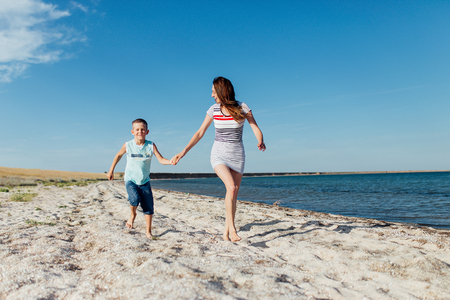 Funny portrait of a happy family on the beach. Mother is holding his son by the hand, they are running on the seashore and smiling.
