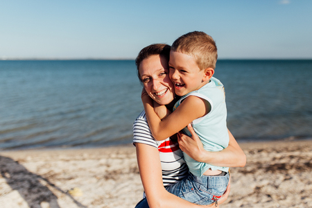 Funny portrait of a happy family on the beach. Mother is holding his son on her hands, they are embracing and smiling, looking at the camera.