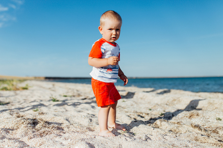 Portrait of a little boy on the beach. He is standing on the sand and looking at the camera.