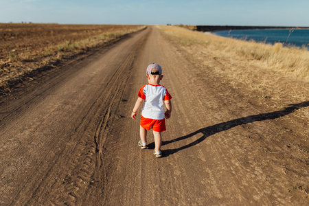 Portrait of a little boy on the road near the sea. He is walking on the road and standing back to the camera. Zdjęcie Seryjne - 122890023