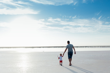 Portrait of a little boy with his father on the beach. They are walking to the sea back to the camera. Stockfoto