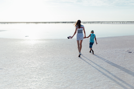Portrait of a little boy with his mother on the beach. They are walking to the sea back to the camera.