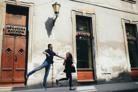 Lovely portrait of a young couple. They are walking in the city, standing near the old building, moving, jumping and smiling. Stock fotó