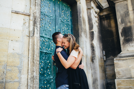 Lovely portrait of a young couple. They are walking in the city, standing near the old building, embracing each other and smiling. Banque d'images - 122887230
