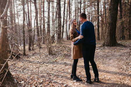 Beautiful portrait of a pregnant woman and her husband. They are walking in the forest, embracing and looking at each other. Stok Fotoğraf