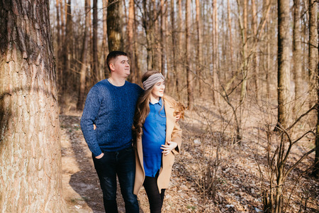 Beautiful portrait of a pregnant woman and her husband. They are walking in the forest, embracing and looking away. Stok Fotoğraf