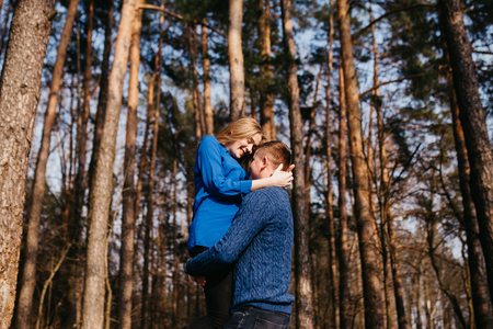 Beautiful portrait of a pregnant woman and her husband. They are walking in the forest and a man is holding his wife on his hands. They are smiling. Stok Fotoğraf
