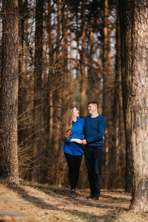Beautiful portrait of a pregnant woman and her husband. They are walking in the forest, holding their hands and looking at each other. They are smiling.