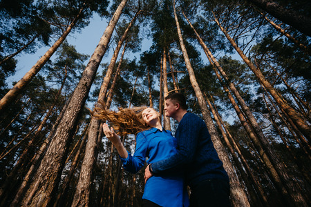 Beautiful portrait of a pregnant woman and her husband. They are walking in the forest, embracing each other and smiling.