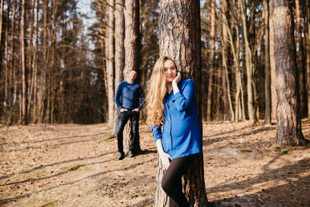 Beautiful portrait of a pregnant woman and her husband. They are walking in the forest, standing far from each other near the trees and smiling.