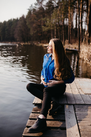 Beautiful portrait of a pregnant woman in the forest. She is sitting near the river, holding her tummy and looking away. Reklamní fotografie