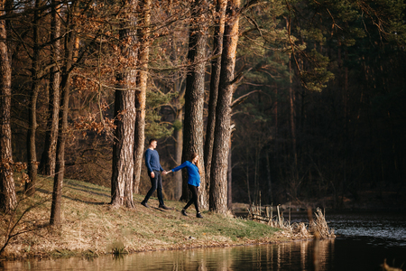 Beautiful portrait of a pregnant woman and her husband. They are walking in the forest, standing near the river, holding their hands.