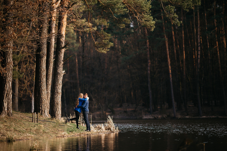 Beautiful portrait of a pregnant woman and her husband. They are walking in the forest, standing face to face near the river, embracing and looking at each other. Imagens