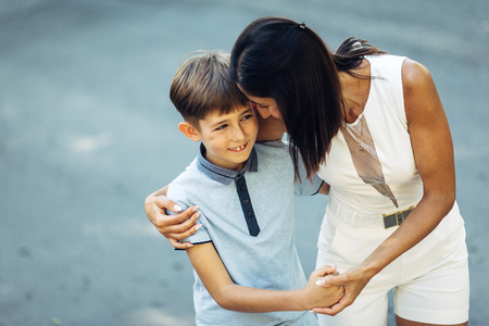 Portrait of a young happy mother and her little son. They are walking, standing on the street, embracing and smiling.