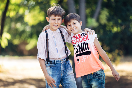 Portrait of a two little brothers. They are standing in the park, embracing and smiling. Stockfoto