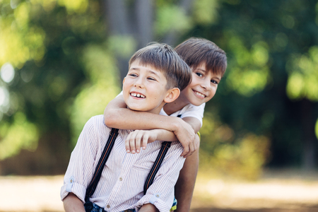 Portrait of a two little brothers. They are sitting on the bench, embracing and smiling.