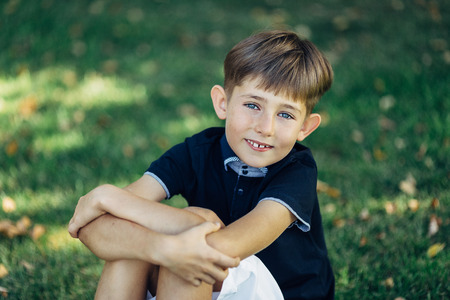 Portrait of a cute little boy. He is sitting on the grass, crossing his hands, looking at the camera and smiling.