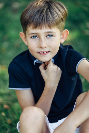 Portrait of a cute little boy. He is sitting on the grass, looking at the camera and smiling.