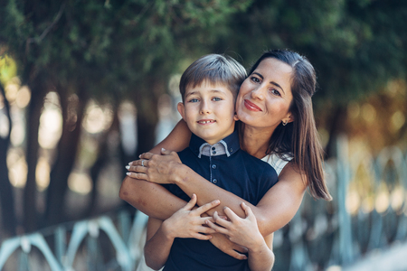 Portrait of a young happy mother and her little son. They are walking in the park, standing near the tree, embracing, looking at the camera and smiling. Stockfoto