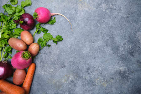 Turnip, cilantro, potatoes, carrots and red onions on a dark background