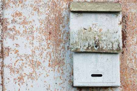 Old mailbox for paper letters. Rusted metal blue wall.