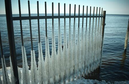 The iron grating is covered with ice in the sea