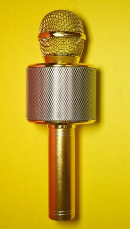 Gold metal karaoke microphone on a yellow background close-up, positioned vertically