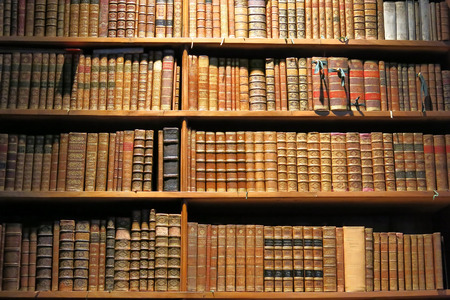 Old books standing on library shelf photo