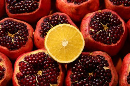 garnets: Yellow lemon laying on red numerous fresh garnets