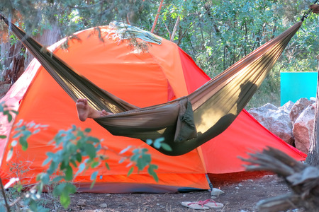 Man laying in the hammock near the tent in the forest