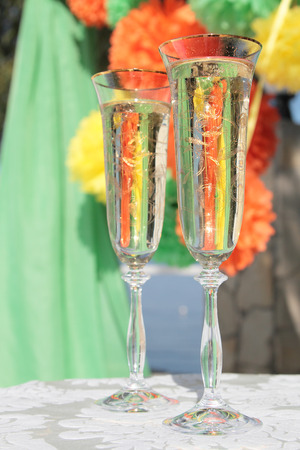 Two wedding glasses of champaign on the colorful background