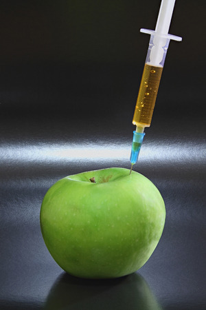 Green apple with syringe on the black background