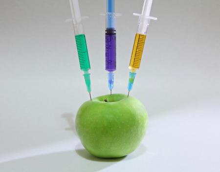 Green apple with syringes on the white background Archivio Fotografico