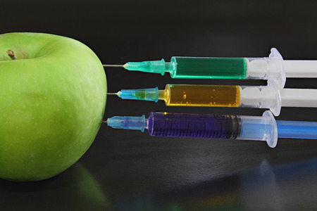 Green apple with syringes on the black background