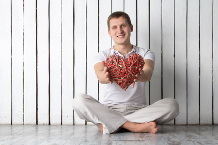 Man with hand-made red wooden heart sitting near the wall